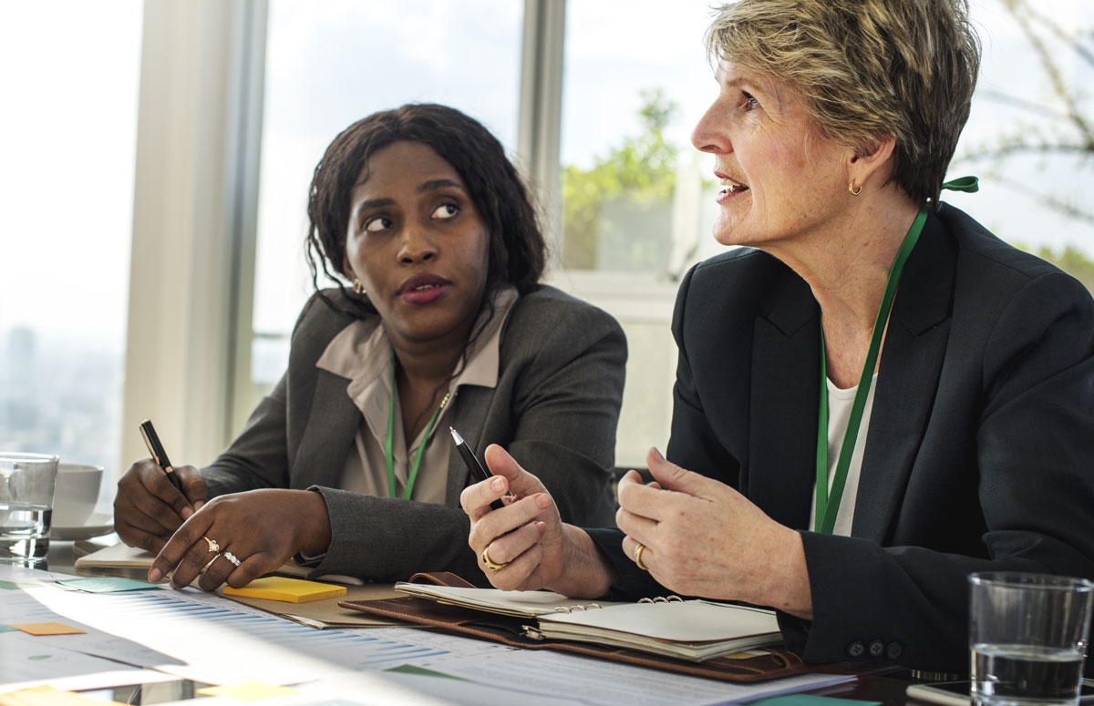 Two women at a conference table speaking