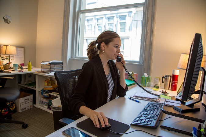 Photo of woman at desk on phone
